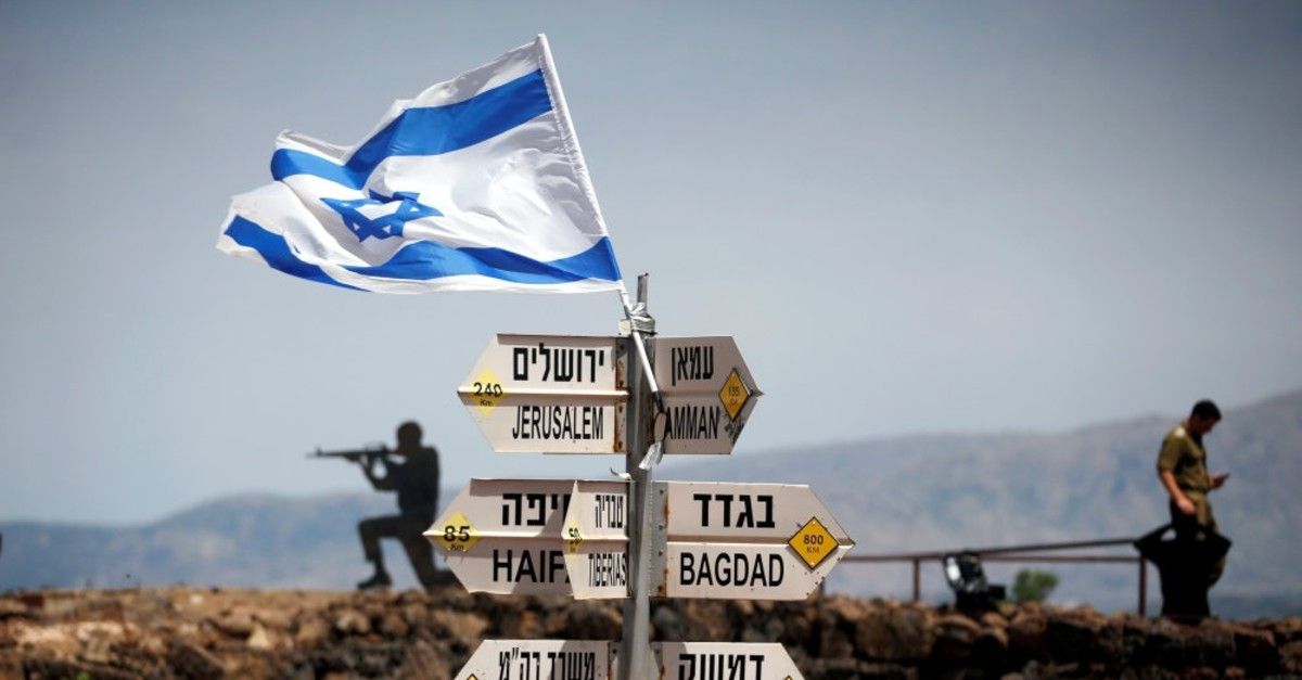 An Israeli soldier stands next to signs pointing out distances to different cities on Mount Bental, an observation post in the Israeli-occupied Golan Heights that overlooks the Syrian side of the Quneitra crossing, May 10, 2019.