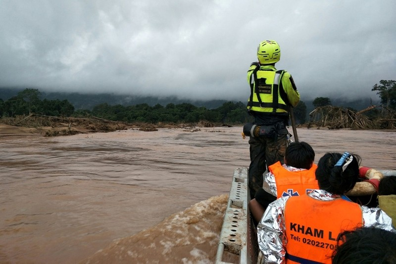 This July 26, 2018 handout photo released July 27, 2018 shows a member of the Thai Rescue Team volunteer group riding in a raft with rescued flood survivors close to the swollen river in Attapeu province, Laos. (AFP Photo/Thai Rescue Team)