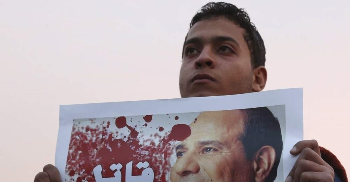 A demonstrator holds a poster of Egyptian President Abdel Fattah el-Sissi with the word ,Killer, written on it during a silent protest, Cairo, Feb. 14, 2015. (REUTERS Photo)