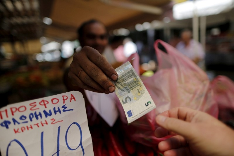 A vendor gives a five Euro bank note back to a customer at the central market in Athens, Greece, July 8, 2015. (Reuters Photo)