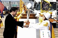 South Korean first torchbearer and figure skater Young You (R) receives the olympic torch of the PyeongChang 2018 Winter Olympic Games from South Korean Prime Minister Lee Nak-Yeon (L) on the Incheon bridge in Incheon, South Korea. (EPA)