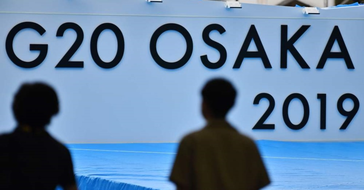 People stand in front of a stage set up for participants at the venue for the G20 Osaka Summit in Osaka, June 26, 2019.