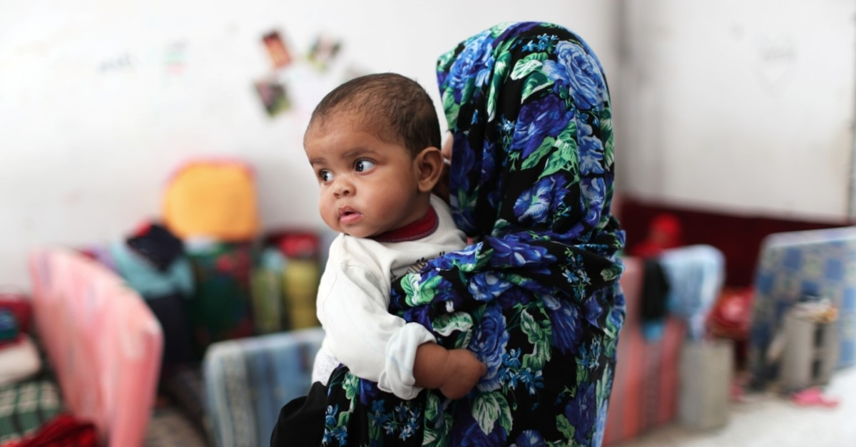 A migrant woman carries her baby at the Anti-Illegal Immigration Agency in Tajora shelter center, Tripoli, April 24, 2019.