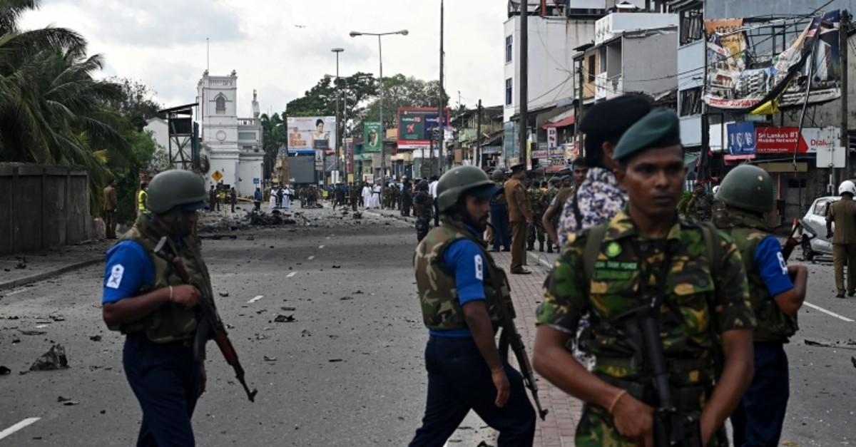 Sri Lankan soldiers stand guard as security personnel inspect the debris of a car after it explodes when police tried to defuse a bomb near St. Anthony's Shrine in Colombo on April 22, 2019. (AFP Photo)