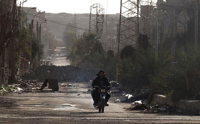 Men ride a motorbike along a deserted street filled with debris in Deir el-Zour, eastern Syria, March 7, 2014. (Reuters Photo)