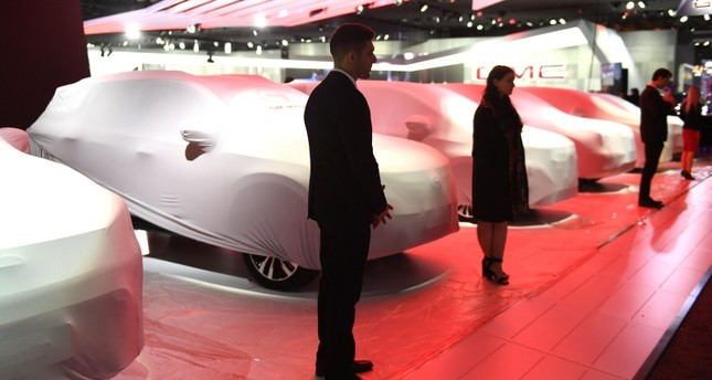 People prepare for their unvieling at GAC Motor in the Cobo Center in  Detroit Michigan January 13, 2019 (AFP Photo)