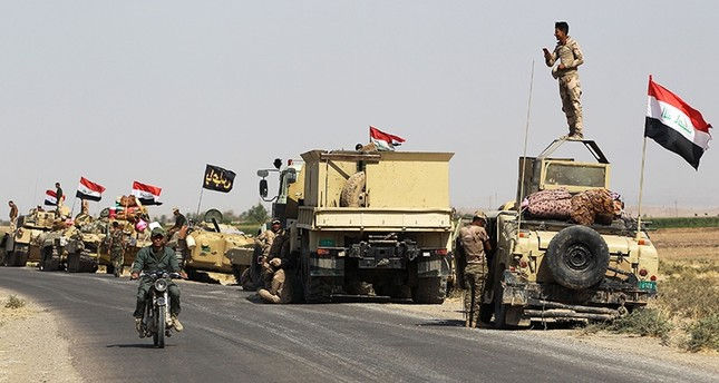 Iraqi forces rest on the road as they drive towards Kurdish peshmerga positions on October 15, 2017, on the southern outskirts of Kirkuk. (AFP Photo)