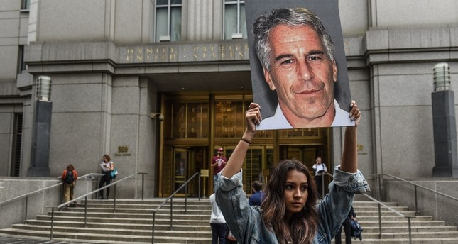 A protest group called Hot Mess hold up signs of Jeffrey Epstein in front of the federal courthouse on July 8, 2019 in New York City. (AFP Photo)