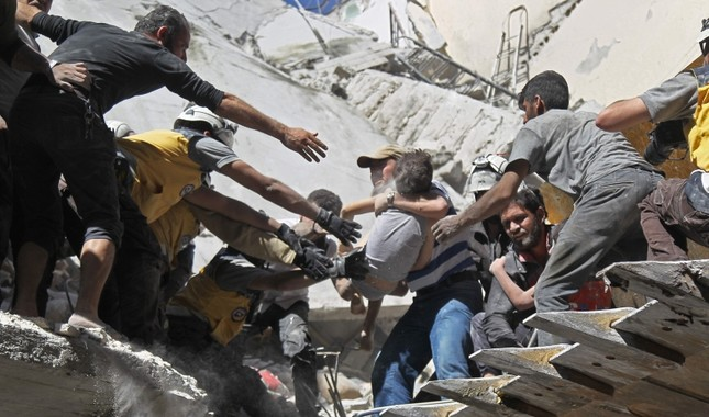 White Helmet volunteers and civilians rescue a child from the rubble of a building destroyed during an airstrike by the Assad regime forces and their allies in Ariha, southern Idlib province, Syria, May 27, 2019. AFP Photo