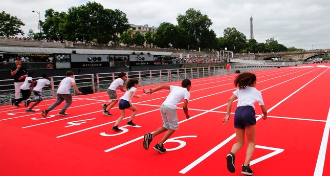 Children take the start in a 100m race on an athletics track installed on the River Seine in Paris, during an event to promote the candidacy of the city of Paris for the Summer Olympics Games in 2024.