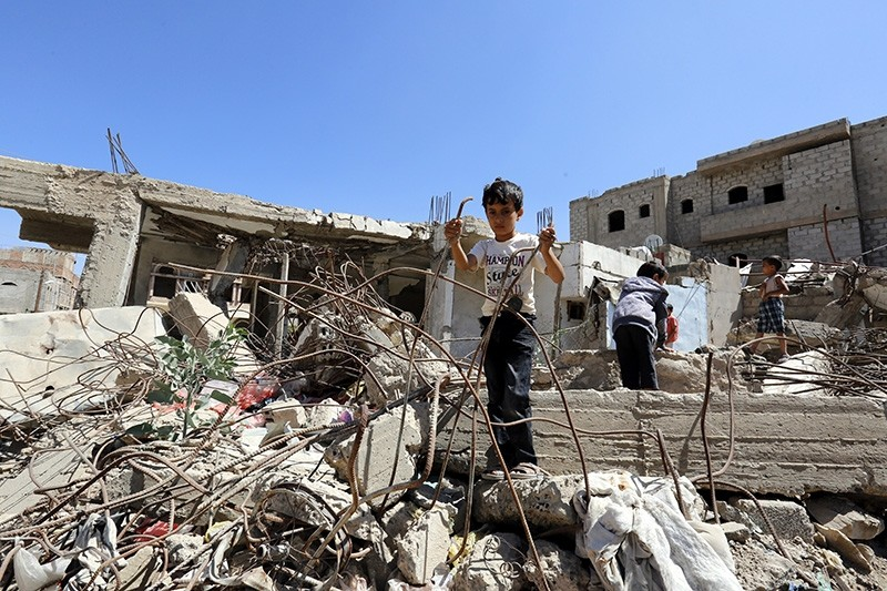 A Yemeni child stands on severely damaged ruins of a house that reportedly was destroyed by Saudi-led airstrikes, at a neighborhood in Sana'a, Yemen, 07 October 2017 (EPA Photo)