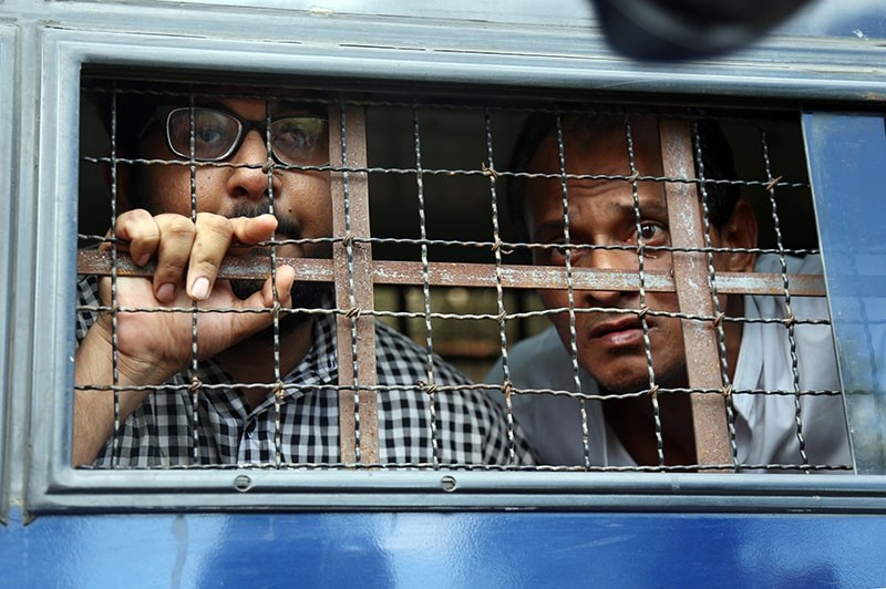 Aung Naing Soe (L), Myanmar freelance journalist and interpreter, and their driver Hla Tin(R), leave after at Zabu Thiri court during their first trial in Naypyitaw, Myanmar 10, November 2017. (EPA Photo)