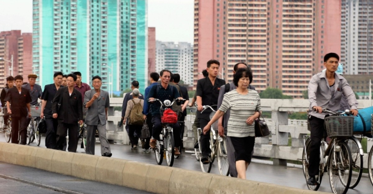 Men and women walk on a bridge as apartment buildings are seen in the background during the morning rush hour in Pyongyang, North Korea, Friday, June 15, 2018. (AP Photo)