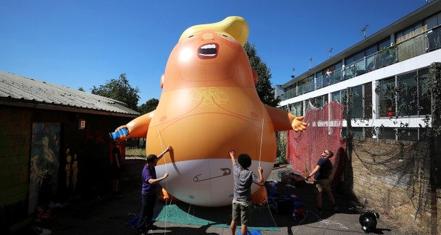 People inflate a helium filled Donald Trump blimp which they hope to deploy during The President of the United States' upcoming visit, in London, Britain, June 26, 2018. (REUTERS Photo)