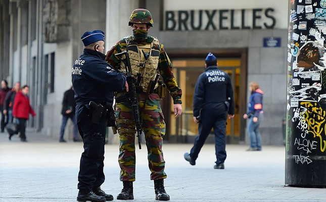A Belgian soldier speaks to a police officer outside Brussels Central Station as people are allowed in small groups of ten to reach the station in order to take their commuter train following attacks in Brussels on March 22, 2016. (AFP Photo)