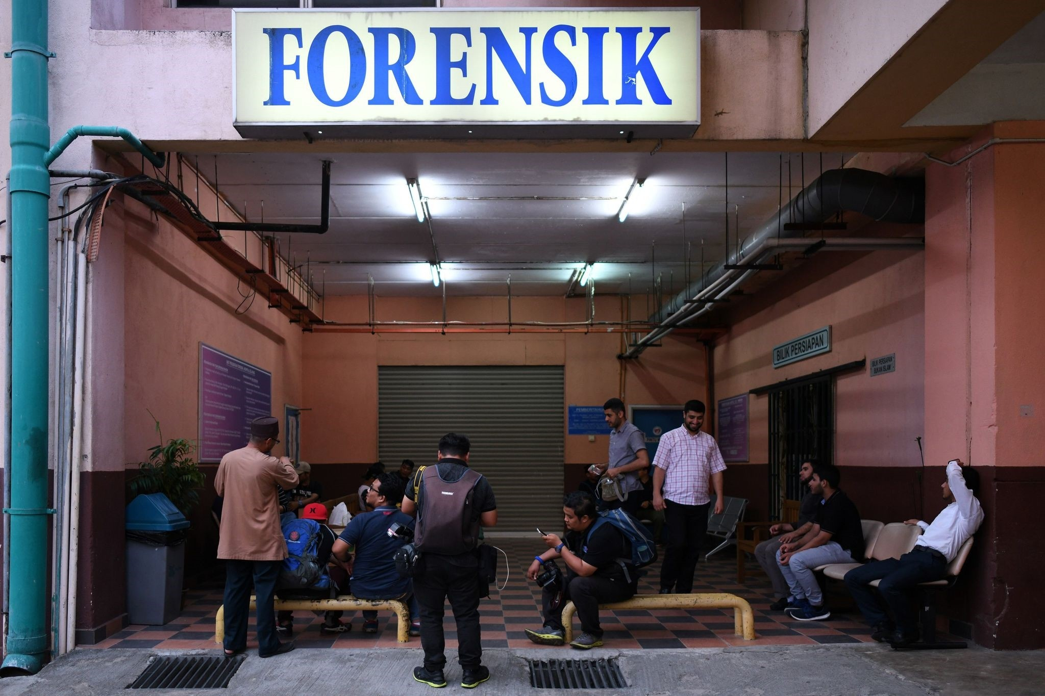 Members of the media wait outside the compound of the forensic wing of the Hospital Selayang, where the body of Palestinian professor Fadi Mohammad al-Batsh is being kept, in Kuala Lumpur on April 22, 2018. (AFP Photo)