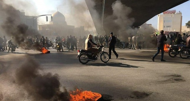 Iranian protesters rally amid burning tires during a demonstration, Isfahan, Nov. 16, 2019. AFP Photo