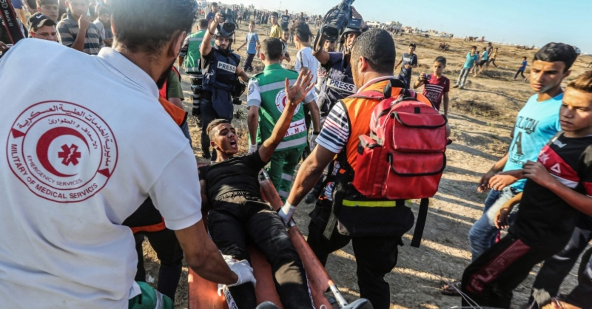 Palestinian paramedics carry away on a stretcher a protester who was injured during clashes with Israeli forces following a demonstration along the border with Israel east of Gaza City on September 27, 2019 (AFP Photo)