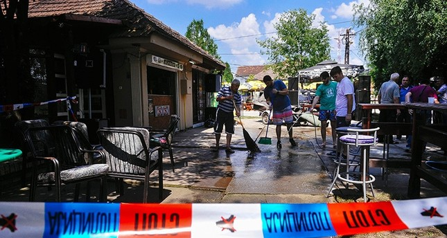 People clean up the ground behind a police ruban at a cafe after a man shot dead five people in the village of Zitiste, northern Serbia on July 2, 2016 AFP Photo