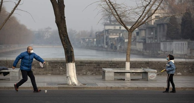 A man and girl wear face masks as they play badminton near the closed Forbidden City in Beijing, Jan. 27, 2020. AP Photo