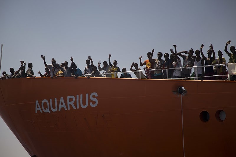 In this photo taken on Sunday, Aug. 21, 2016, migrants wave from SOS Mediterranee Aquarius rescue ship, after being rescued by members of the Spanish NGO Proactiva Open Arms during an operation at the Mediterranean Sea. (AP Photo)