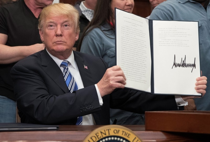 US President Donald J. Trump signs a presidential proclamation on aluminum tariffs in the Roosevelt Room of the White House in Washington, DC, USA, 08 March 2018. (EPA Photo)