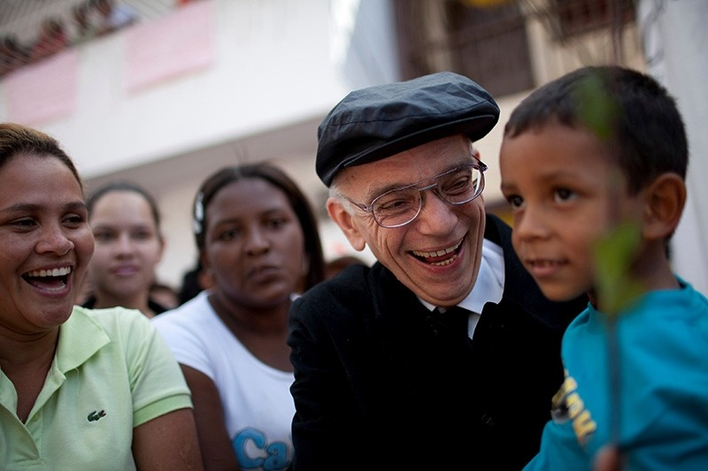 Founder of the National System of Youth and Children's Orchestras of Venezuela, Jose Antonio Abreu carries a child as he arrives at a free concert at the low-income neighborhood of La Vega in Caracas, on August 2, 2009. (Reuters Photo)