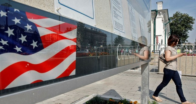 A woman walks by a board with consular information outside the US embassy in Moscow on August 22, 2017. (AFP Photo)