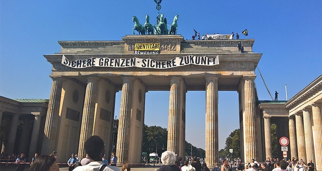 Anti-Islam activists have staged an hour-long demonstration atop Berlin's Brandenburg Gate Saturday Aug. 27, 2016. (AP Photo)