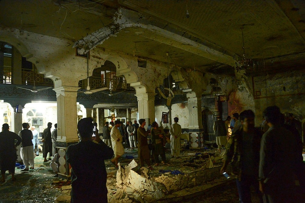 Afghan security personel inspect the site of a suicide bomb attack at a Shiite mosque in Herat, Afghanistan, Aug. 1, 2017.