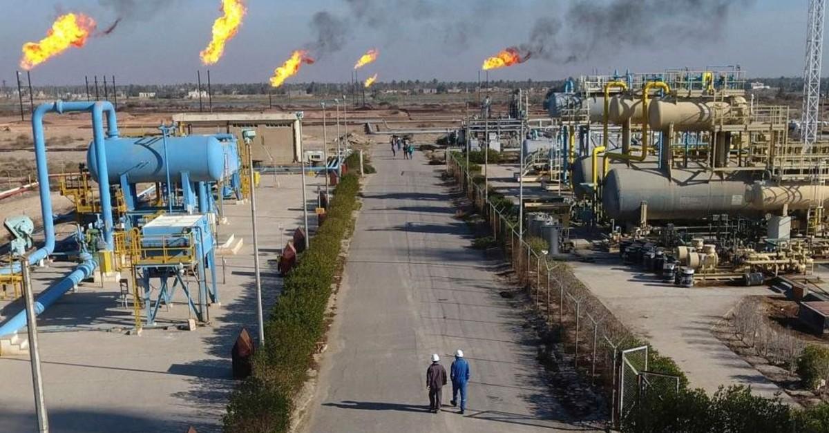 In this Thursday, Jan. 12, 2017 file photo, laborers walk in the Nihran bin Omar Field near Basra, Iraq (AP Photo)