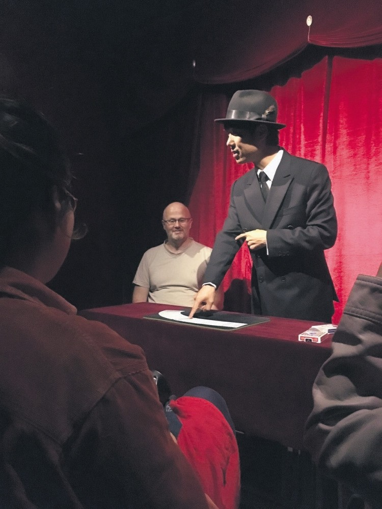 A magician taking stage at Magic Lamp.