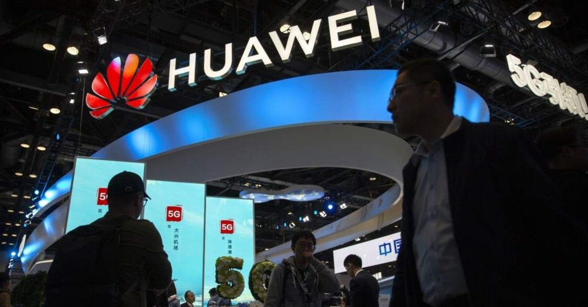 In this Oct. 31, 2019 file photo, attendees walk past a display for 5G services from Chinese technology firm Huawei at the PT Expo in Beijing. (AP Photo)