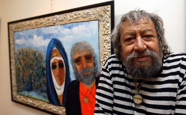 Fikret Otyam poses in front of one of his paintings.