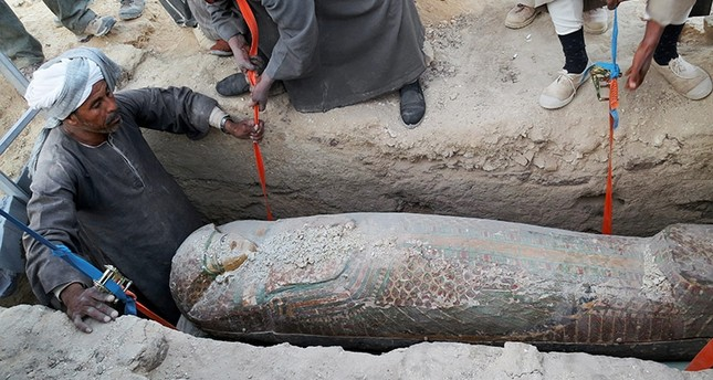 This photo released on Thursday, Feb. 13, 2014  shows Egyptian men digging up a preserved wooden sarcophagus that dates back to 1600 BC, when the Pharaonic 17th Dynasty reigned, in the ancient city of Luxor, Egypt. (AP Photo)