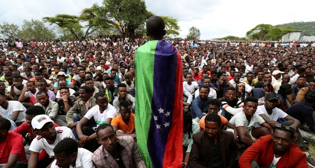 A Sidama youth leader draped in a flag addresses people as they gather for a meeting to declare their own region, Hawassa, July, 17, 2019.