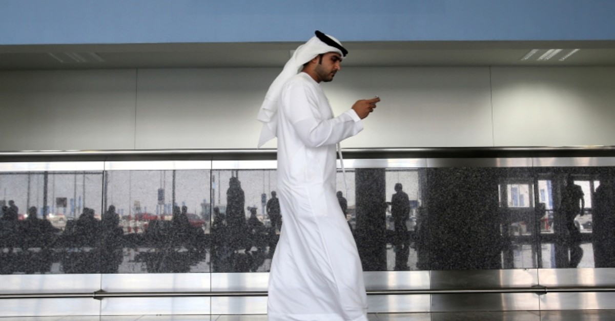 In this Oct. 27, 2013 file photo, a worker looks at his mobile phone at the newly opened Al Maktoum International Airport in Dubai, United Arab Emirates. (Patrick Castillo/Emarat Al Youm via AP, File)