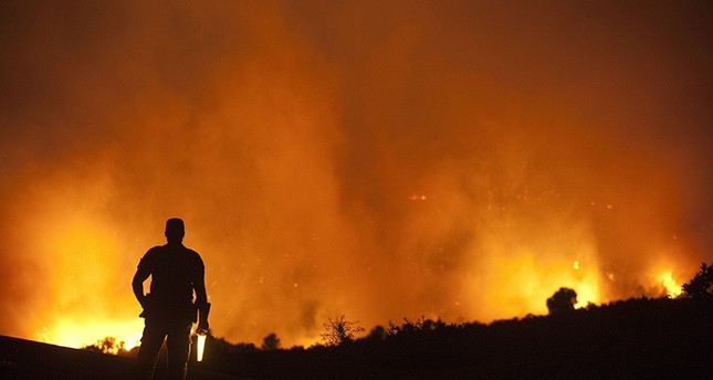 A police watches early on September 24, 2012 a fire blazing in a forest near the city of Domeno, near Valencia (AFP Photo)