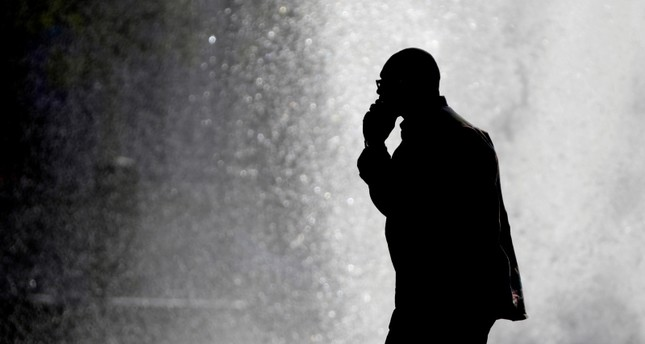 In this Thursday, Oct. 11, 2012 file photo, a pedestrian talking on a cellphone is silhouetted in front of a fountain in Philadelphia. (AP Photo)