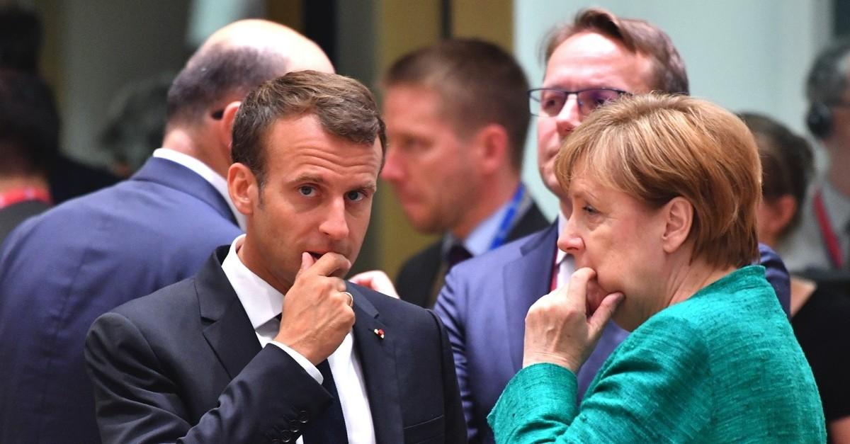 German Chancellor Angela Merkel speaks with French President Emmanuel Macron at an EU summit, Brussels, June 28, 2018.