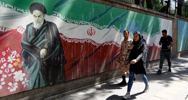 A woman walks past a mural painting showing the founder of Iran Ayatollah Ruhollah Khomeini and the national flag along the wall of the former US embassy in the Iranian capital Tehran on June 22, 2019. (AFP Photo)