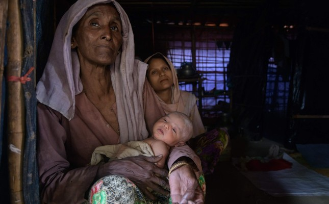 A Rohingya refugee sits behind her eight-day-old baby and her mother-in-law at the Thangkhali refugee camp near Cox's Bazar, Aug. 11, 2018.