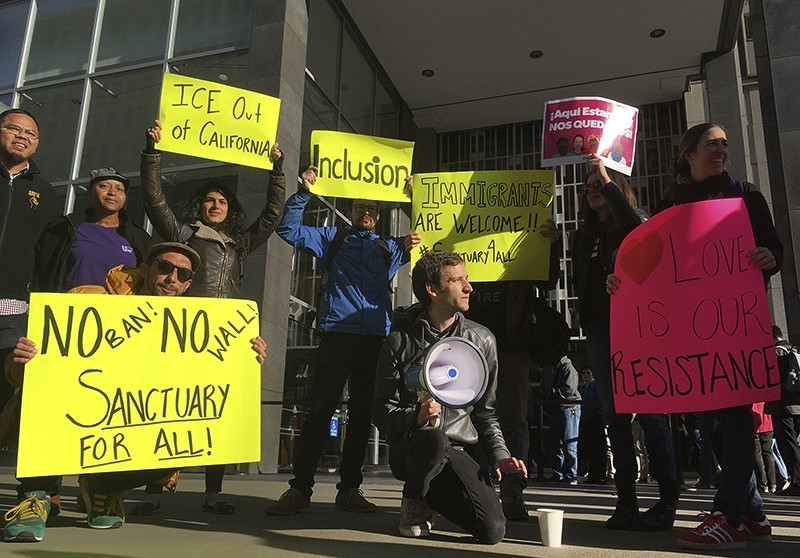 Protesters hold up signs outside a courthouse where a federal judge will hear arguments in the first lawsuit challenging Trump's executive order to withhold funding from communities that limit cooperation with immigration authorities (AP Photo)
