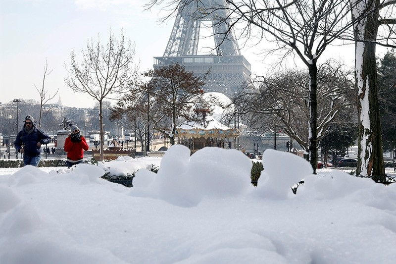 People walk on the snow-covered Trocadero gardens near the Eiffel Tower in Paris, as winter weather with snow and freezing temperatures arrive in France (Reuters Photo)
