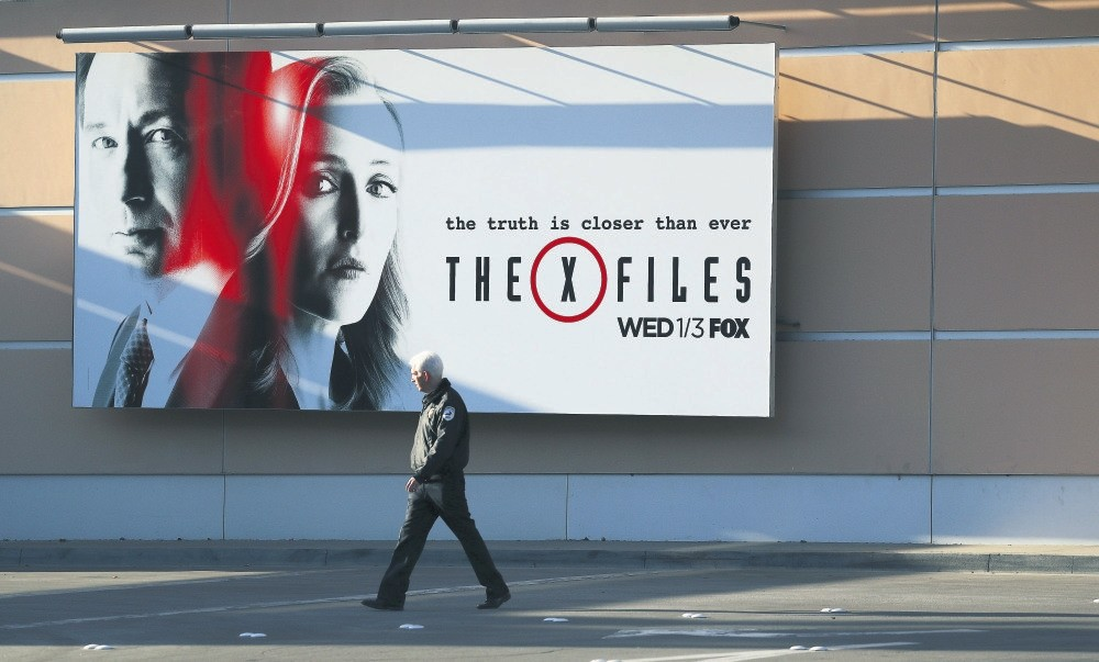 A security guard walks past a billboard for u2018The X Files' on the lot of 20th Century Fox in Century City, Califorinia.