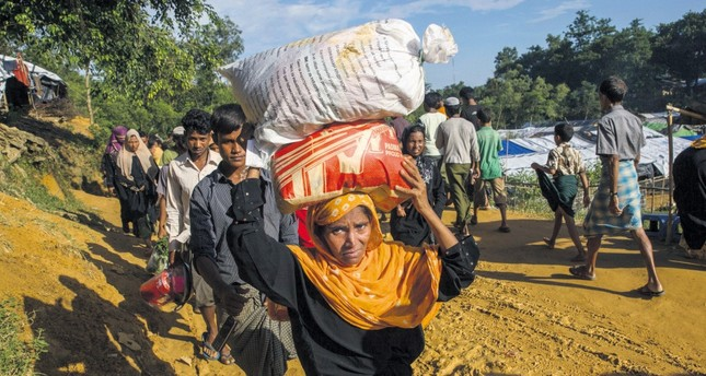 A Rohingya Muslim woman, who crossed over from Myanmar into Bangladesh, walks back to her shelter after collecting aid at Kutupalong refugee camp, Bangladesh.