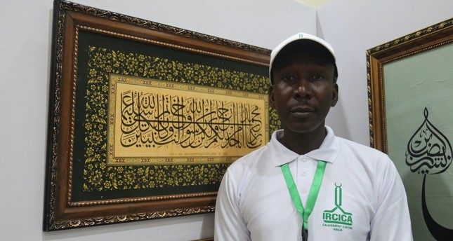 Yushaa Abdullah poses in front of his works.