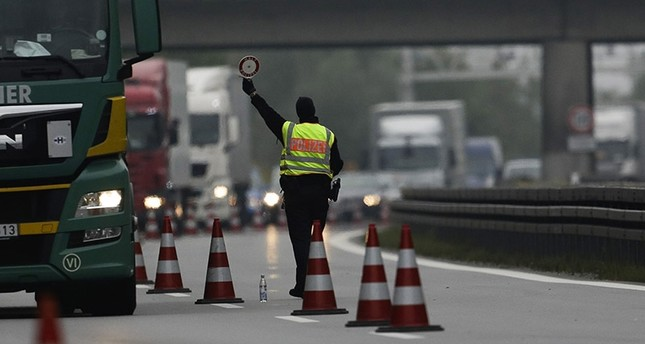 A German Federal Police officer stands on a street to control cars around the south German border town Passau, Germany, Tuesday, Sept. 15, 2015. (AP Photo)