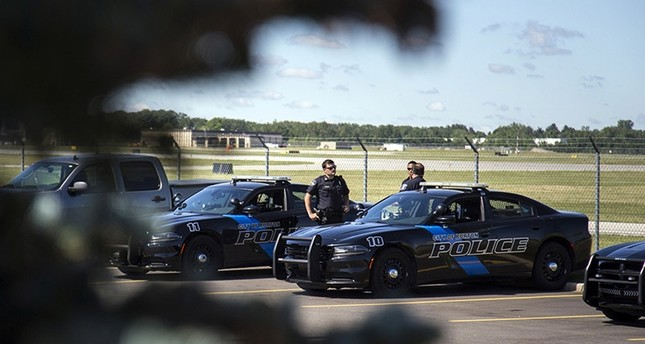 Burton Police Officers gather at Bishop International Airport, Wednesday morning, June 21, 2017, in Flint, Mich. (AP Photo)
