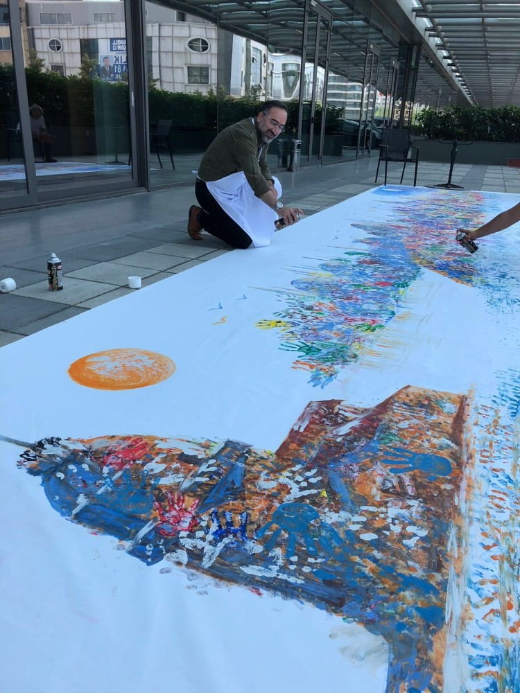 Students used their handprints to color a giant painting of the Istanbul skyline.
